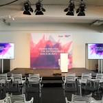 Die Bühne mit Frontlicht, Rednerpult und Flatscreens.